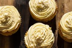 Uma imagem de fundo do creme quatro delicioso coloriu queques em uma placa de madeira Fotografia de Stock Royalty Free