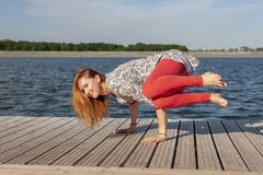 Uma imagem de uma mulher bonita que faz a ioga no lago imagens de stock