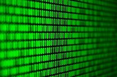 Uma imagem de um código binário compôs de um grupo de dígitos verdes em um fundo preto imagens de stock