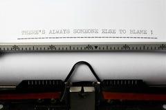 Uma imagem do ` dos theredo alguma outra pessoa sempre à culpa - nós vivemos nós morremos ` escrito em uma máquina de escrever  fotos de stock royalty free