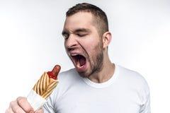 Uma imagem do homem que gosta do fast food oleoso Nesta imagem quer morder uma parte grande do cachorro quente gordo Olhares do h fotografia de stock royalty free