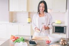 Uma imagem do queijo grating da menina feliz a bordo Olha para baixo e sorri Há plentty dos alimentos frescos na tabela imagens de stock royalty free