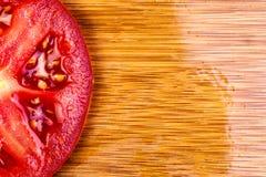 Uma imagem macro de uma única fatia do tomate em uma placa de corte de bambu imagem de stock
