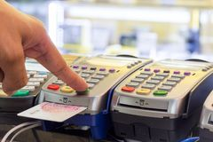 Uma imprensa do dedo no matchine do cartão de crédito na loja Imagem de Stock