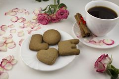 Uma inscrição de uma cookie do amor, café preto, pétalas cor-de-rosa em um petisco branco do fundo fotografia de stock royalty free