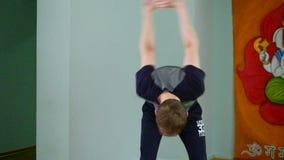 Uma ioga do homem faz um esticão saudável no estúdio filme