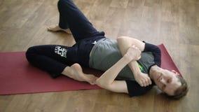 Uma ioga do homem faz um esticão saudável no estúdio vídeos de arquivo