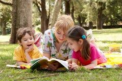 Uma irmã mais idosa lê às crianças do livro Foto de Stock Royalty Free