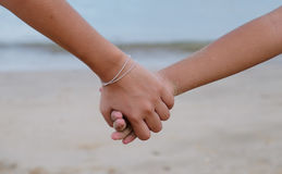 Uma irmã que guarda seu brother& x27; mão de s na praia Imagens de Stock Royalty Free