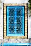 Uma janela antiga com um ornamento e um ferro azul que raspam na AR Imagens de Stock