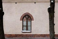 Uma janela de uma igreja em uma parede vazia entre duas árvores fotos de stock royalty free