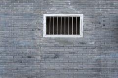 Uma janela na textura cinzenta do fundo da parede de tijolo Imagem de Stock