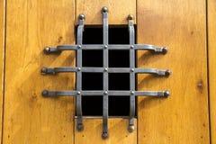 Uma janela pequena com barras de metal em uma porta de madeira antiga, spain foto de stock