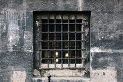 Uma janela pequena com uma estrutura em uma igreja velha Uma vela é ardente fora do windo Fotos de Stock Royalty Free