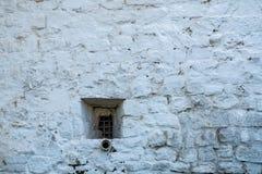 Uma janela pequena na parede de pedra Fotos de Stock