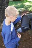 Uma jovem criança que olha dentro a uma caixa postal. imagem de stock