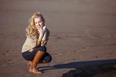 Uma jovem mulher é de assento e de sorriso com olhos fechados Imagem de Stock