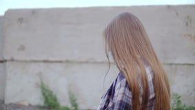 Uma jovem mulher anda ao longo da cerca e olha às vezes na câmera video estoque