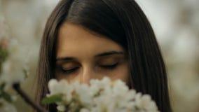 Uma jovem mulher anda através do jardim da mola e aprecia o perfume das flores de Apple vídeos de arquivo