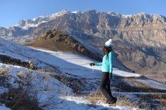 Uma jovem mulher anda nas montanhas em um inverno bonito imagens de stock