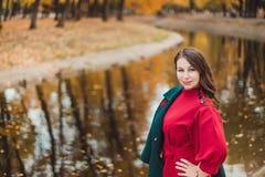 Uma jovem mulher anda no parque do outono Mulher moreno que veste um revestimento verde e um vestido vermelho fotos de stock