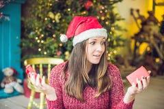 Uma jovem mulher aprecia seu presente de Natal Venda do Natal fotografia de stock