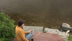 Uma jovem mulher aprecia um telefone que senta-se em um cais pela lagoa no verão filme