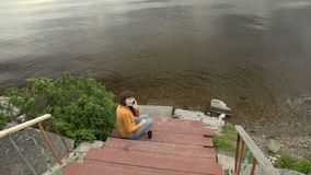 Uma jovem mulher aprecia um telefone que senta-se em um cais pela lagoa no verão vídeos de arquivo