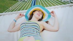Uma jovem mulher atrativa está tomando sol em uma rede Mulher no conceito foto de stock royalty free