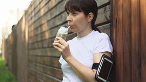 Uma jovem mulher bebe batidos da desintoxicação antes ou depois do treinamento no por do sol filme
