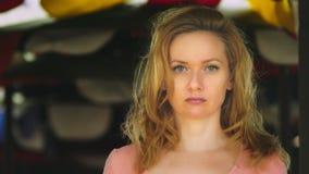 Uma jovem mulher bonita com cabelo louro está estando em um espaço aberto em um dia ventoso que olha atentamente na câmera cópia video estoque