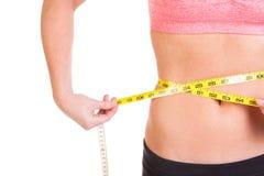 Uma jovem mulher bonita com a fita de medição da gestão do peso Foto de Stock
