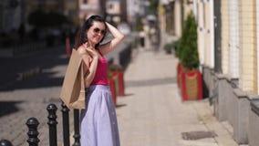 Uma jovem mulher bonita com um saco de papel gerencie ao redor e sorri após o movimento 4k lento de compra vídeos de arquivo