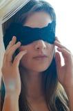 Uma jovem mulher bonita do encanto com a faixa preta do laço na venda da cara Fotos de Stock