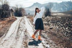Uma jovem mulher bonita em uma saia cinzenta e em umas caminhadas das botas de borracha através de um prado no país Dança, rir te fotos de stock
