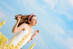Uma jovem mulher bonita em um campo de trigo foto de stock royalty free