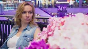 Uma jovem mulher bonita está sentando-se em um banco em um grande shopping moderno perto de uma cama de flor video estoque