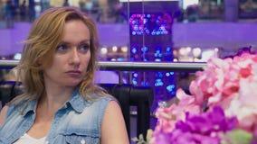 Uma jovem mulher bonita está sentando-se em um banco em um grande shopping moderno perto de uma cama de flor filme