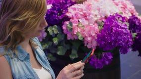 Uma jovem mulher bonita está sentando-se em um banco em um grande shopping moderno perto de uma cama de flor usa-a video estoque