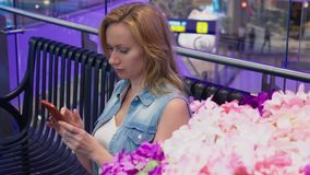 Uma jovem mulher bonita está sentando-se em um banco em um grande shopping moderno perto de uma cama de flor usa-a filme