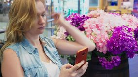 Uma jovem mulher bonita está sentando-se em um banco em um grande shopping moderno perto de uma cama de flor usa-a vídeos de arquivo