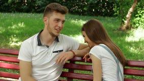 Uma jovem mulher bonita fala e ri com um indivíduo em um banco no parque video estoque