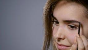 Uma jovem mulher bonita penteia sua sobrancelha Forma bonita da beleza da tração da mulher das sobrancelhas usando a escova cosmé vídeos de arquivo