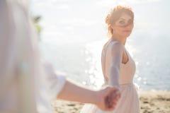 Uma jovem mulher bonita, posses a mão do homem no ar livre Siga-me O embaçamento é criado para o quadro romântico fotografia de stock