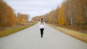 Uma jovem mulher bonita que anda no meio da estrada vídeos de arquivo