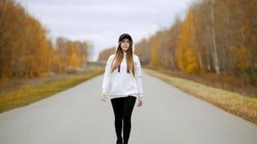 Uma jovem mulher bonita que anda no meio da estrada outono filme