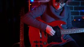 Uma jovem mulher bonito está jogando na guitarra elétrica vermelha perto da parede de tijolo filme