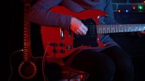 Uma jovem mulher bonito está jogando na guitarra elétrica vermelha perto da parede de tijolo video estoque