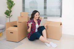 Uma jovem mulher com as caixas da tabuleta e de cart?o que movem-se em uma casa nova fotos de stock royalty free