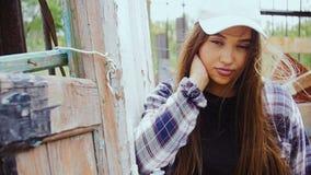 Uma jovem mulher com cabelo longo e um boné de beisebol está estando pela cerca velha filme